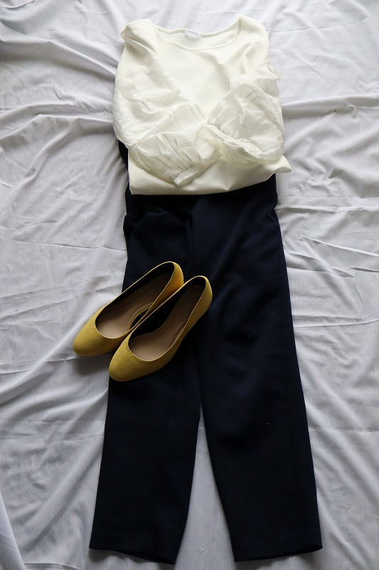 白いブラウスのファッションにからし色のパンプスを合わせたコーディネイト例