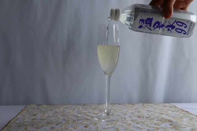 ワイングラスはいった優光泉に水を注いでいるところ